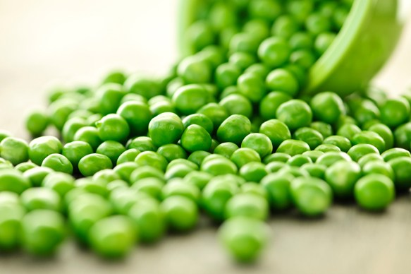 Closeup on spilling bowl of fresh green green peas